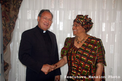 President Sirleaf greets visiting CRS official.