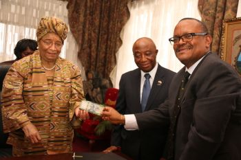 CBL Executive Governor, Weeks, President Sirleaf display new LD$100.00 banknote as VP Joseph Boakai looks on.