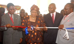 President Sirleaf cuts the ribbon to the facility as outgoing Post and Telecommunications Minister Jackson Doe (l) and others look on.