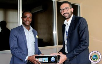IOM Office in Charge Amr Nagy presents supplies to Min Trokon Kpui.