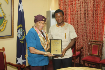 Mr. Mambu Johnson who also attended the meeting presents his award to President Sirleaf.