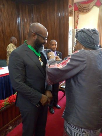 President Sirleaf Honors Mr. Richelieu Dennis.