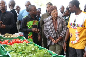 President Sirleaf accompanied by Commerce Minister Addy inspects made in Liberia products.