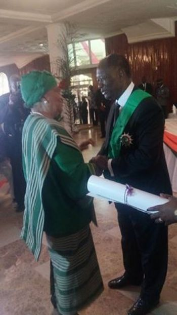 President Sirleaf admits Ivoirian President Ouattara into Order of the Knighthood of the  Pioneer.