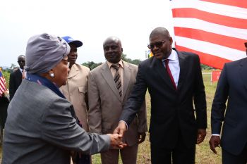 President Sirleaf greets LAA Board Chair Gbehzonguy Findley on arrival for ground-breaking ceremony.
