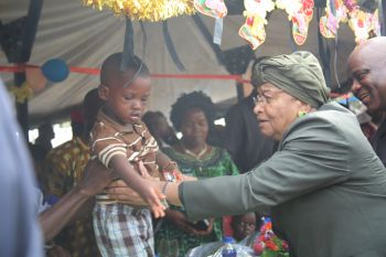 President Sirleaf happily lifts a child during the AFL Affiliation Day Program on Tuesday.