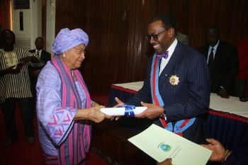 President Sirleaf presents certificate of honor to Dr. Adesina at the Investiture ceremony.