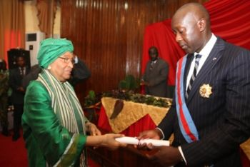 President Sirleaf presents certificate to Minister Konneh.