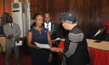 President Sirleaf presents certificate to a female graduate.