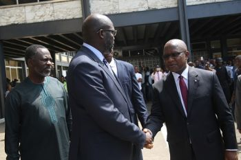 President Weah is greeted by Chief Justice Francis Korkpor on the grounds of the Temple of Juctice