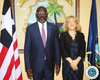 Swiss Confederations Ambassador poses with President Weah for official photo after presenting her letter of credence