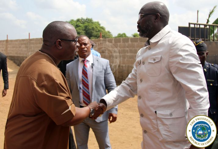 President Weah greets Montserrado District One Representative Lawrence Morris at the dialogue