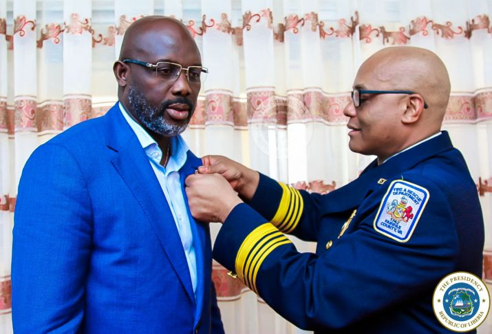US Fire Marshall, John Butler pins President Weah with United States Fire Department flag pin