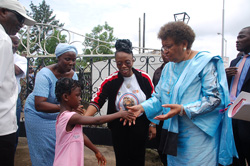 President Sirleaf is received on the grounds of the Capitol Building by a young kid.