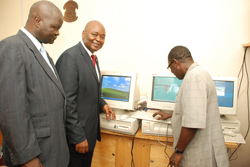 UL President  Alhassan Conteh and Assistant Chief of Staff for Logistics (Varney Sirleaf) take a look at the computers, as Prof. Joe Mulbah looks on.